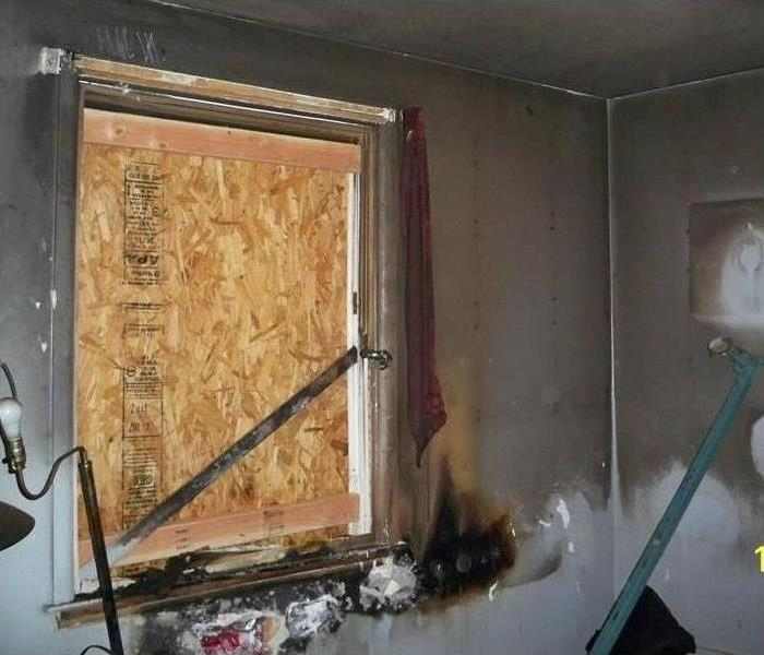 Boarded up window in a home with substantial fire damage